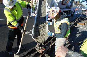 Pouring concrete for curbs and gutters on Airport Rd. near 112th St.
