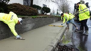 Crews pour concrete for a new sidewalk along the south side of 75th St., then ensure a smooth finish and 1.2 percent slope.