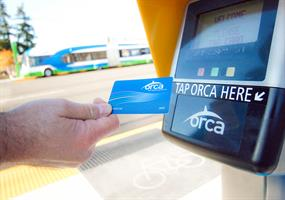 A customer swipes his ORCA card at a Swift Station.